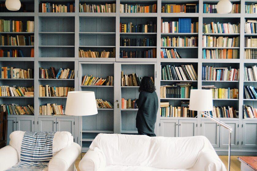 Kobieta przy regałach z książkami, zdjęcie ilustracyjne