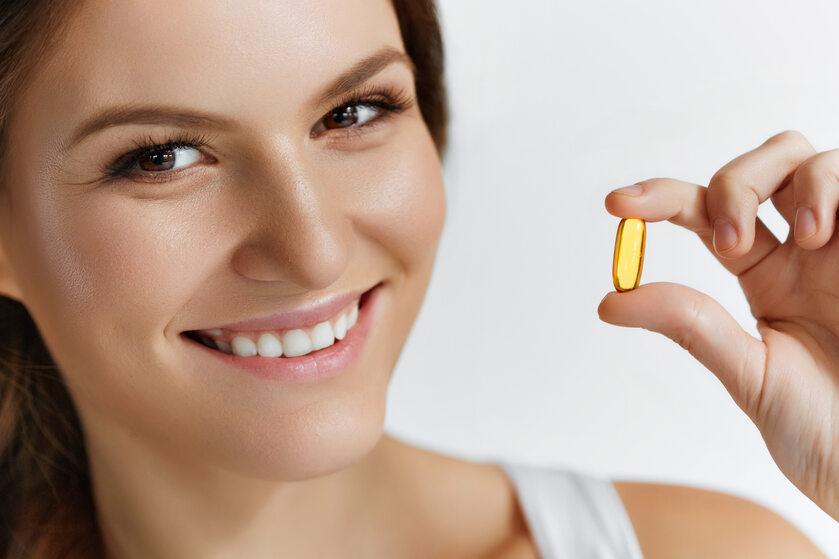 Uśmiechnięta kobieta suplementuje witaminę D